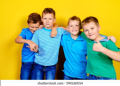 Four boys best friends standing together. Bright yellow background. Summer fashion.