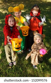 Four boys in halloween costumes trick or treating