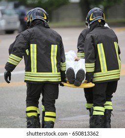 Four brave firemen transport the injured with a stretcher far from the accident site to make it safe