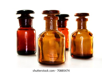 four brown apothecary bottles against a white background