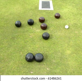 four brown and four black bowls and jack lying on green with matt
