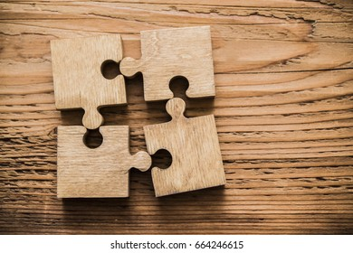 Four brown pieces of puzzle lie on wooden table background. empty copy space for inscription or objects.