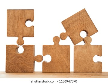 Four brown wooden pieces of puzzle standing against white background. empty copy space for inscription or objects. isolated on white background.