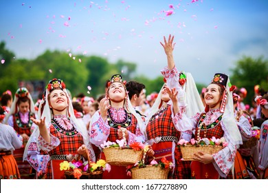Four Bulgarian girls dressed in traditional clothing throwing rose in the air during the Annual Rose Festival in Kazanlak / Bulgaria - 1 June 2018