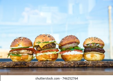 Four burgers on wooden board in restaurant