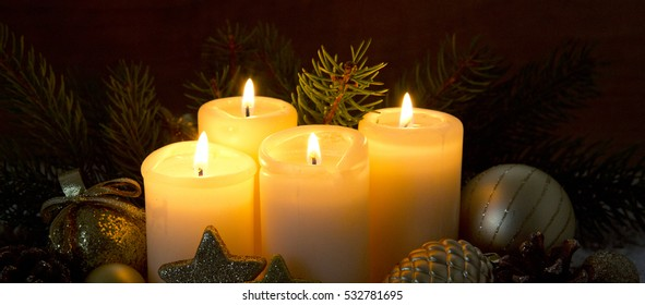 Four burning advent candles and Christmas decoration.