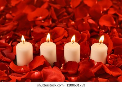 four burning candles stand in red rose petals