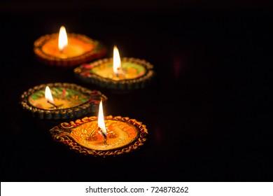 Four burning colorful clay diya lamp Diwali celebration. Black background. Selective focus.