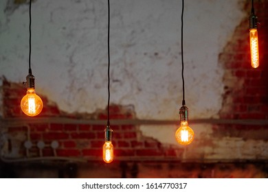 four burning light bulbs of various shapes hanging on long black wires
