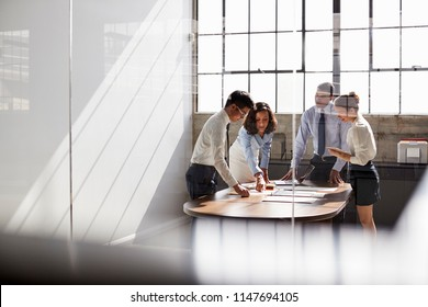 Four business colleagues stand talking in a meeting room