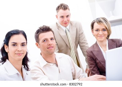 Four business colleagues working together on laptop computer in office, looking at camera, smiling.