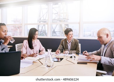 Four business executives integrate technology in a meeting early in the morning at the conference table next to a large window with bright natural light coming in.