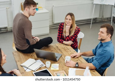 Four business partners having a relaxed meeting in a spacious office grouped around a table chatting in a high angle view