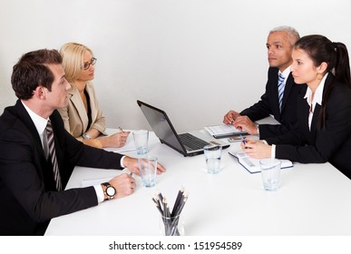 Four business people discussing in the meeting