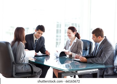 Four business people during a meeting sitting around a table