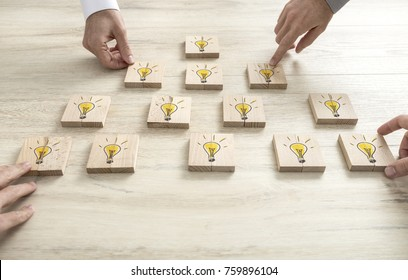 Four business people placing wooden blocks with yellow light bulbs in a form of a pyramid. Conceptual of brainstorming, creative thinking and teamwork.