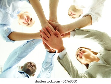 Four business people putting their hands on hands of their colleagues
