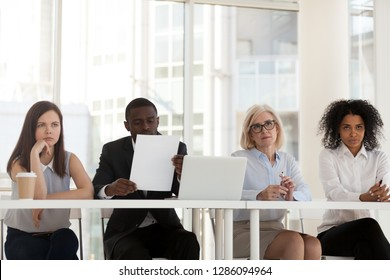 Four business people serious confused multinational recruiting agency workers sitting at desk looking at applicant skeptical and with disbelief. Bad first impression and failing job interview concept