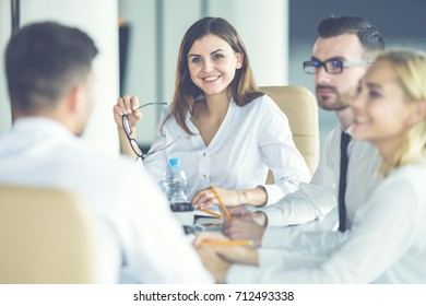 The four business people sit at the table and discuss