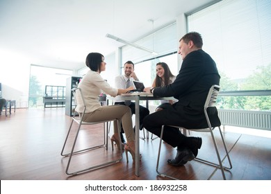 Four business people sitting around office table