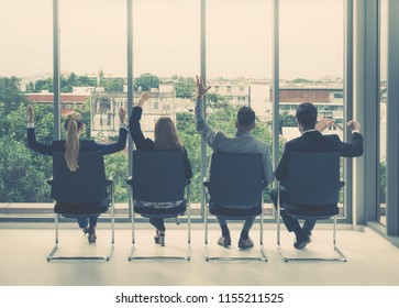 Four Business people sitting back facing windows in meeting