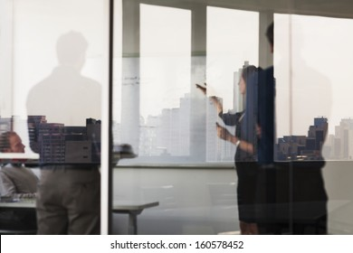 Four business people standing and looking at  white board on the other side of glass wall