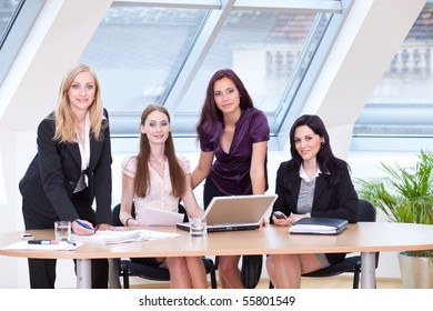 four business women with laptop at the desk