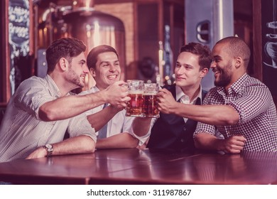 Four businessmen drink beer and rejoice together at the bar. Confident business people having fun with friends at the bar with a beer.