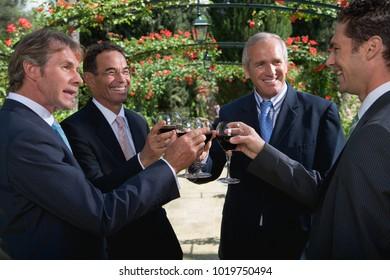 Four businessmen drinking wine