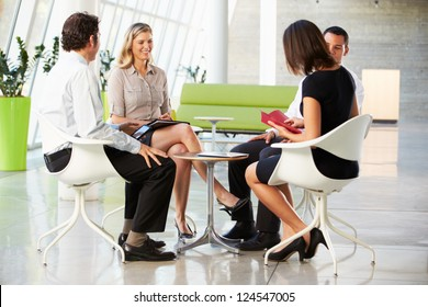 Four Businesspeople Having Meeting In Modern Office