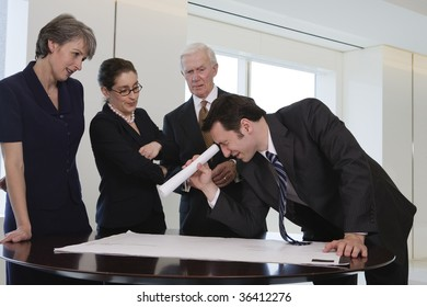 Four businesspeople in an office conference room.