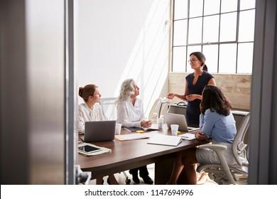 Four businesswomen in meeting,  seen from doorway