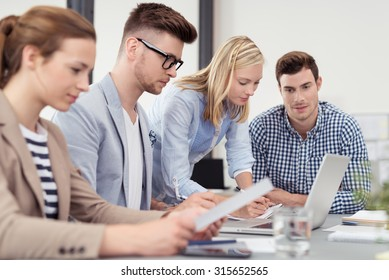 Four Busy Young Office People Having a Business Meeting inside the Boardroom