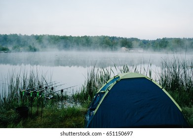 Four carp fishing rods in rod pod on a background of lake and nature. Fishing background. Carp fishing. Misty morning. nature. Holder rods. Wild areas. Blue tent. Signaling devices. Old house