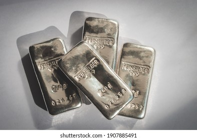 Four cast silver bars on a gray background. feinsilber is fine silver.
