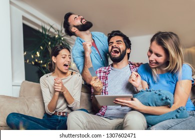 Four casual happy friends laughing shopping online together in a tablet sitting on a sofa in the living room at home