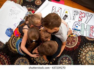 Four Caucasian Children Hug a Baby Boy on the floor of their Home