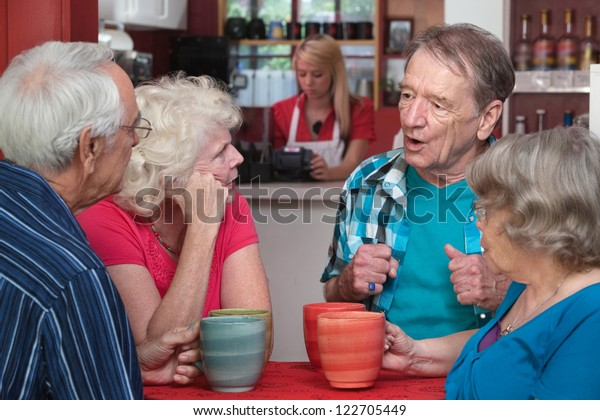 Four Caucasian senior adults with coffee mugs in conversation