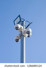 Four CCTV dome security cameras and two LED floodlight on a pole in sky
