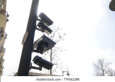 four cctv installed on metal light pole, blue sky background