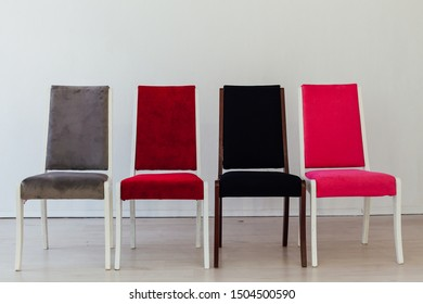 four chairs stand in an empty white room