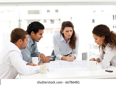 Four charismatic architects looking at plans together around a table