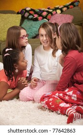 Four chatty little girls in pajamas at a sleepover