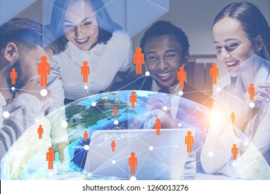 Four cheerful business people working together in office with Earth and global people network hologram in foreground. Toned image double exposure Elements of this image furnished by NASA
