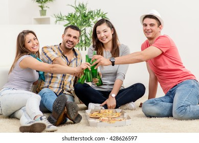 Four cheerful friends hanging out in an apartment. They drinking beer and eating pizza. Looking at camera.