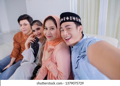 Four cheerful Muslim people taking photo together during Eid Mubarak celebration. Shot at home