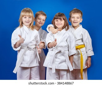 Four cheerful sportsman in karate gi are showing finger super