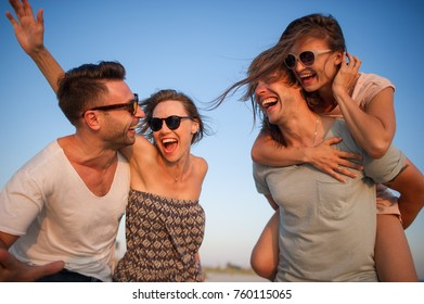 Four cheerful young people against the background of the blue sky. Two girls and two guys with pleasure spend free time. Cheerful weekend.