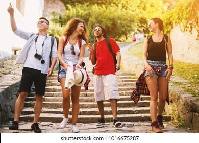 Four cheerful young people going down the big rocky stairs on a vacation in an old town.