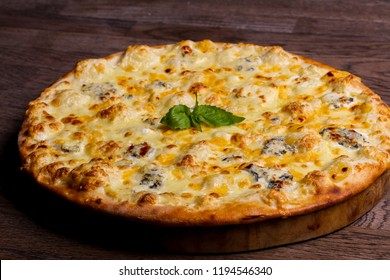 Four cheese pizza served basil